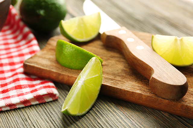 Freshly cut limes on wooden board with knife