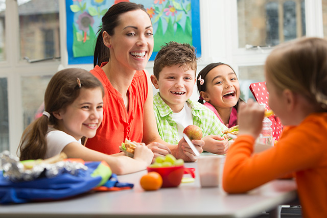 Children eating healthy food with adult around table